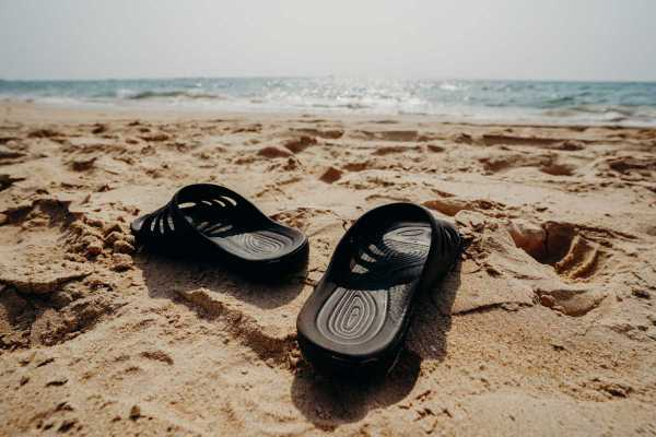 black-and-white-adidas-slide-sandals-on-brown-sand-4427149